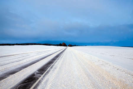 a real photo of a highway with traces in the frosty winter weather after snowfalls, a dangerous time to travel