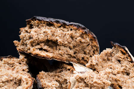 broken into pieces dark bread with a crisp crust on a wooden table, a loaf of delicious homemade bread with soft and fragrant flesh