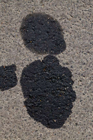 oil black spots on the asphalt of the road from cars in need of repair, environmental pollution from human action, transport breakdowns Stock fotó