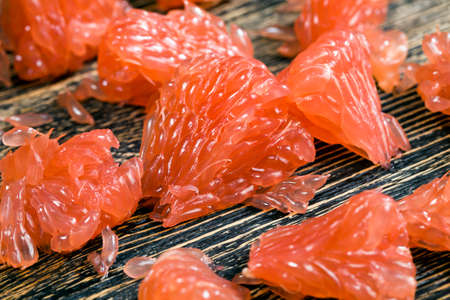 a piece of peeled grapefruit on a wooden table, close-up of fresh red grapefruit pulp Foto de archivo
