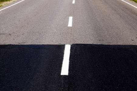 light old and black new paved road connected during the construction or reconstruction and repair of the roadway, on the asphalt is applied a line of white road markings
