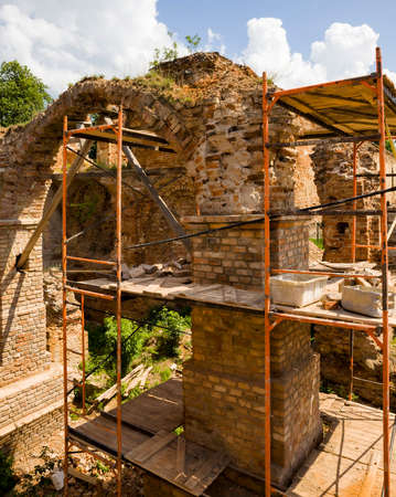 old brickwork of different bricks and ruined and dilapidated arches, is part of the old castle, the restoration of the fortress, scaffolding installed Stok Fotoğraf