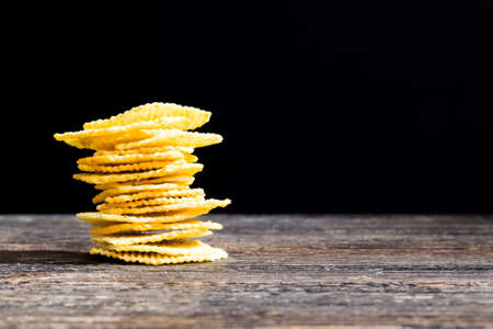 pile of yellow and crispy, green-spiced potato fluted chips on a wooden table, abstract background, close up