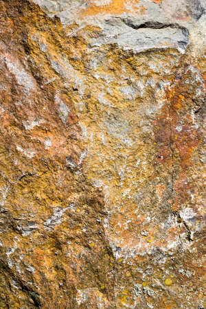 the structure of the real broken apart rusty yellowish stone with hollows and uneven surface, close-up of one stone with damage