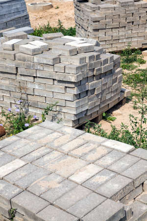 Packed large and long new concrete blocks for curbs and pavers lie on the ground at the construction site PRRI building a new road