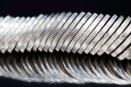 unknown large quantity pile of beautiful old coins with ribbed side, lie together, close-up photo of real metal money illuminated by light