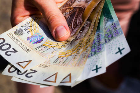 several new banknotes worth one hundred and two hundred Polish zlotys, close-up of cash Polish money together in the hands of a person