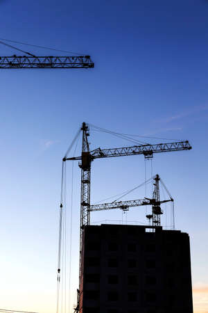 high yellow construction crane on the construction site for the construction of a multi-storey building, during the sunrise Banco de Imagens