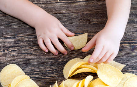real crispy and salty potato chips ready to eat, close-up of unhealthy food products, mashed potato chips in the hand of a child