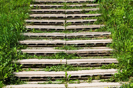 improvised stairs made of improvised materials, concrete slabs and structures with cracks and other damages, green grass grows between the slabs