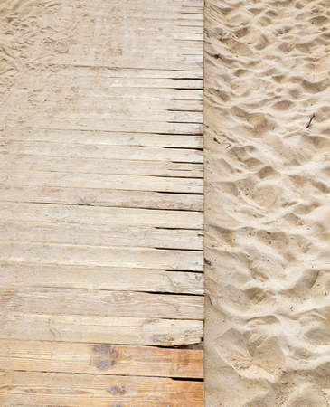 wavy uneven structure of sand on the beach by the sea, close-up of soft fine sand on the seashore, daytime with a wooden road Banco de Imagens
