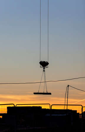 tall yellow construction crane on a construction site in the construction of multistory buildings, photo during sunset
