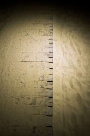 wavy uneven structure of sand on the beach by the sea, close-up of soft fine sand on the seashore, night time with a wooden road