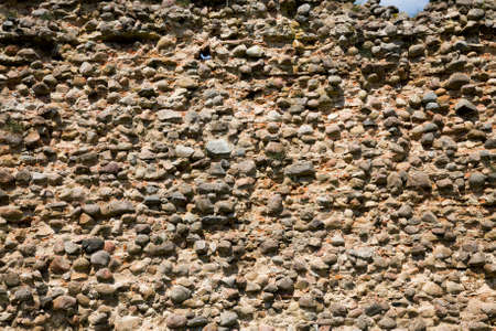part of the wall of a building made of stones and cobblestones, old city buildings