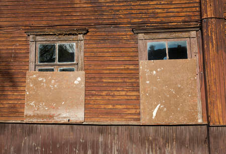 abandoned old wooden house with clogged and closed Windows, part of an old residential building
