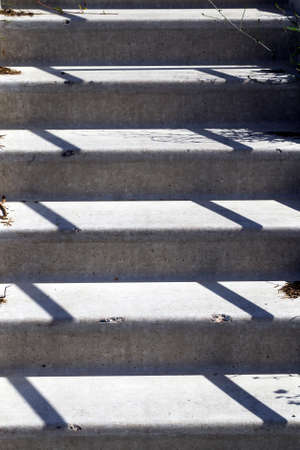 concrete stairs with shadows from nearby railings
