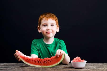a small boy bites watermelon