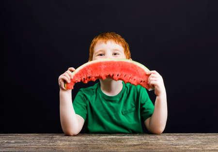 a boy eats a ripe red watermelon