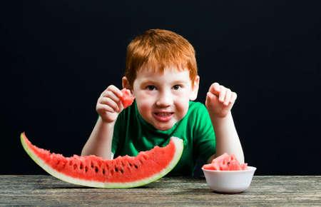 boy eats a red watermelon