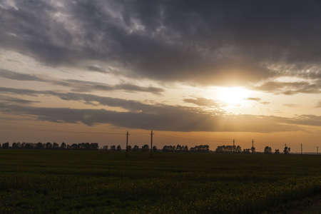 landscape during sunset or dawn with different colors in the sky and the sun that hides behind the horizon, twilight during sunset or dawn, out of focus Stock Photo