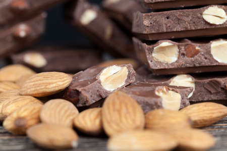 almonds and chocolate mixed in sweet chocolate made from cocoa and cocoa butter with nuts, almonds roasted and added in large quantities to sweets, quality delicious chocolate with nuts, closeup 스톡 콘텐츠