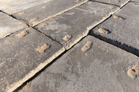 old concrete floors in the construction site of new houses, construction site laid with huge heavy slabs for the movement of construction equipment and vehicles carrying large-sized construction materials and equipment