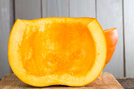 ripe orange pumpkin cut into pieces while cooking vegetarian dishes, sweet pumpkin chunks on a cutting board in the kitchen 스톡 콘텐츠
