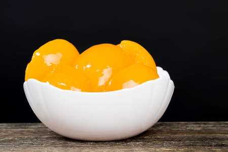 canned ripe orange peaches, fruit preserved in sweet syrup with sugar, peaches are delicious and without skin, close up