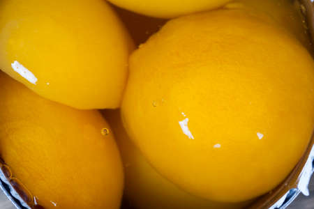 canned ripe orange peaches, fruit preserved in sweet syrup with sugar, peaches are delicious and without skin