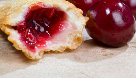 sweet liquid cherry jam in the dough of the baked bun, lies next to the red ripe cherry berries, ready-to-eat food items Standard-Bild