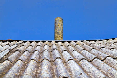 sloping slate house roof with chimney on top against the blue sky, details of the house Standard-Bild