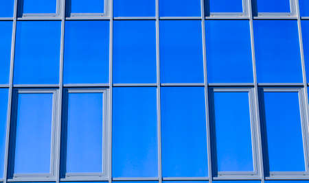 part of the wall of the building sheathed outside with mirror glass of blue color, modern constructions