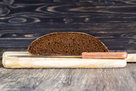 black rye bread cut in chunks on a cutting Board, close-up of traditional food in Eastern Europe