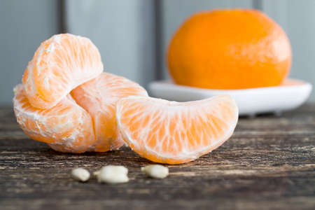 slices of tangerine without peel lying on the table during dessert, close-up of orange citrus, sweet tangerines and not sour