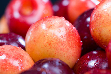 Multicolored ripe berries of a sweet cherry lying in a heap, close-up of natural food from a homemade orchard