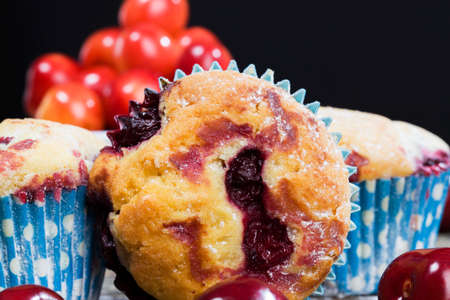 sweet and delicious cupcakes with whole ripe cherries inside, close-up of food and desserts, high-quality industrial baking