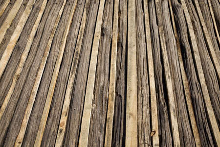 old wooden floor on the ground outside, close-up of rough boards in mud and sand, closeup of construction Standard-Bild