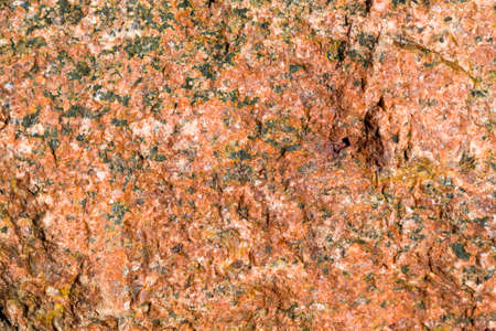 the structure of the natural broken into pieces of red stone with hollows and uneven surface, close-up of one stone with damage
