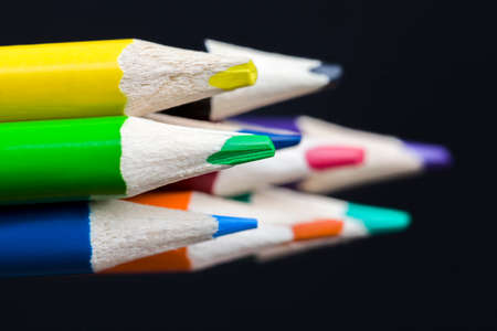 folded multicolored pencils on a black background, wooden pencils are well sharpened for drawing