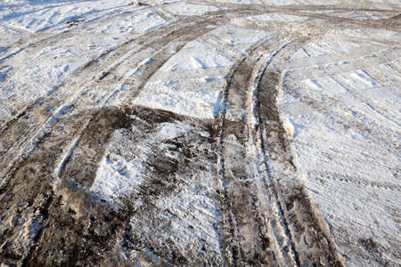 details of snow-covered road in the winter, traces of cars and tracks from transport, close-up on the roadway