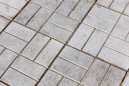 gray concrete tile from which the walking road was built, details in the road park Standard-Bild