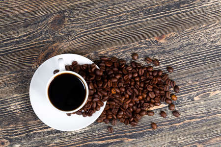beautiful coffee beans ready for the preparation of invigorating drinks, contains caffeine, coffee in a white mug