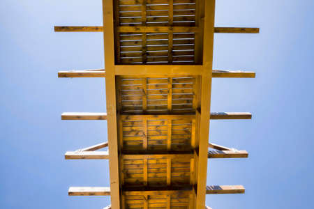 bottom view of a simple wooden bridge over a river against a blue sky in sunny weather