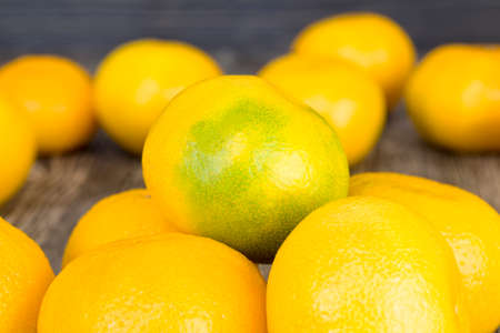 whole large orange tangerines on a wooden Board, close-up of fruit on the table in winter, healthy food
