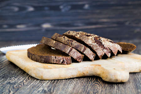baked dark-colored rye flour loaf of bread, cut into pieces during table setting Standard-Bild