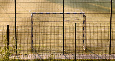 fenced with nets and fences sports grounds for football, close-up of the playing field with a gate