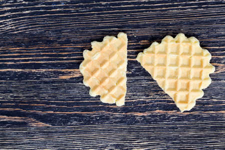 one lying on the wooden surface of wheat sweet waffles, close-up of sweets used as a dessert, half-broken wafer, top view