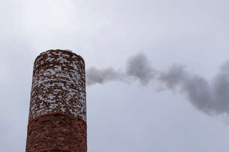 industrial brick pipe from which comes the dark smoke from burning fuel, twilight Standard-Bild