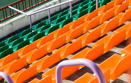 multi-colored plastic chairs set in rows at the stadium for spectators, close-up Standard-Bild