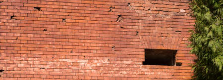 part of the brick wall made in the old castle, close-up of the wall made of a large number of red bricks, old construction abandoned Standard-Bild